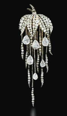 A SUPERB ANTIQUE DIAMOND BROOCH   Of naturalistic design, the pavé-set old-cut diamond leaf canopy suspending a graduated fringe of diamond trails with six pear-shaped diamond drops, mounted in silver and gold, brooch circa 1860, diamond drops late 18th century, 12.7 cm long