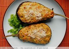 Stuffed eggplant 2 medium or 1 large eggplant Olive oil (for sprinkling) Salt and pepper, to taste 2 tbsp olive oil ½ tsp ground coriander ½ tsp ground cumin 1 clove garlic, finely chopped 2 medium ripe tomatoes, coarsely chopped 1 bay leaf 1 cup paneer or whole milk ricotta (I used crumbled paneer) 1/3 cup finely grated parmesan 1 tbsp chopped fresh cilantro 2 sausages or 2 slices ham, finely diced, or omit this if you're vegetarian (I used chicken sausages) 1 egg, beaten Extra fresh cilantro,