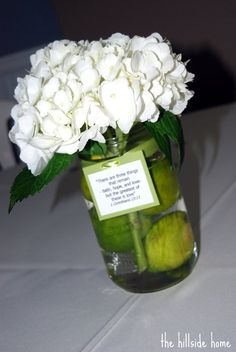 Mason Jar Centerpieces. Nice touch with adding the ribbon with a phrase.