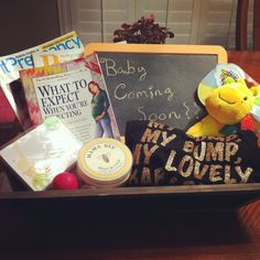 Mom-To-Be gift basket!! Includes: Gender friendly Thank You cards & painted Chalkboard, Parent & Pregnancy magazines, What To Expect book, Mama Bee Belly Butter, Cute Tank top (due in August & we live in Texas), & a Toy for Baby!!