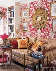 In the library of Alex Papachristidis's Manhattan apartment a 19th-century clock from Charlotte Moss and a Charles H. Beckley sofa. A vintage Chinese cabinet, an antique wicker chair, and gilt steps from Mecox Gardens; the wall covering is by Clarence House.  There is something arresting about the very graphic, red and white Chinese-style wallpaper, set off by white-painted bookcases.