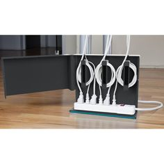 Plug Hub -  a clever station that holds a power strip and plugged-in cords neatly in place behind a hinged door. Slip it behind your desk, mount onto a wall, or organize behind an entertainment system. Features 3 openings on top for cords, 3 integrated cord anchors to wrap and hide long cords, non-slip rubber bottom, and ready-to-mount openings on back. Mounting hardware not included.