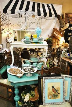 "Turquoise is ""the"" color of the season.  Here it is used effectively to move the eye around a very monochromatic arrangement of disparate items. The studied arrangement of the color through the display is an effective marketing ploy that translates well to decorating a home."