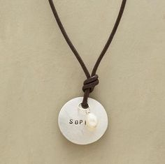 JUST 4 U NECKLACE--Christy Lea Payne stamps the name of your choosing, this distressed disk dangler is purely personal. The sterling silver charm is knotted onto brown leather along with a cultured pearl talisman