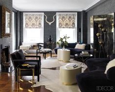 Vladimir Kagan sofas are paired with Karl Springer cocktail tables, the armchair in front is by Milo Baughman, and the lacquered chair's cushion is covered in a Schumacher linen; the walls are papered in grass cloth by Nobilis.