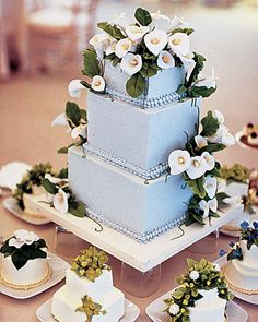 This cake has square layers, pale-blue icing, and sugar calla lilies.