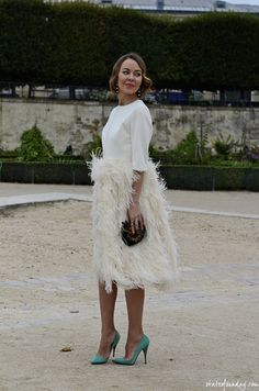 Ulyana Sergeenko. Feather-skirted combined white dress with elbow-length sleeves. Jewel-colored pumps.
