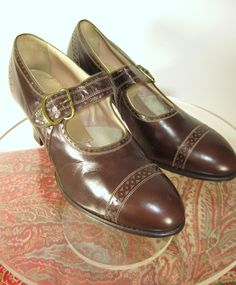 Vintage late 20s into early 30s brown leather brogue-style pumps from the William Porter & Sons shoe company. They feature a thick strap with brass buckle, stacked wooden heels, and geometric Deco punching on the toes and around the heels.