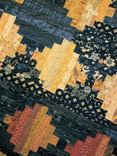 Courthouse steps quilt by KallistiquiltS (etsy) love the quilting swirl on each colour diamond.