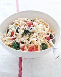 Spaghetti with Spinach, Tomatoes and Goat Cheese | Tossing the cooked spaghetti with some of the reserved pasta cooking water and fresh goat cheese produces a light, tangy and luxurious sauce.