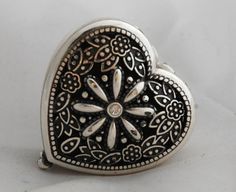 Brighton Silver Heart Shape Pill Box  with a lovely embossed flower and scrolls and open work.   There is engraved work on the bottom side too.   The inside has a nice clean enamel lining.    ...