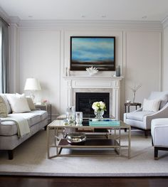 White Living Room 1 with neutral furniture, champagne metallic coffee table and paneled walls  - Gluckstein Home