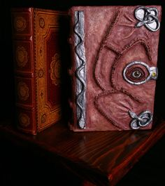 To make this Hocus Pocus inspired spell-book, I took a hollowed-out book from a craft shop and covered it in a polymer clay called Bake-n-Bend, which doesn't harden until baked. I found a pair of mannequin eyes and hand-stitched the cover to look like human skin as described in the movie.