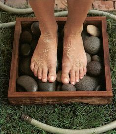 Okay.  Now I need to start gardening ...  river rocks in a box + garden hose = clean feet what a great garden idea! Placed in the sun will heat the stones as well.  Great way to wash off feet before coming inside.
