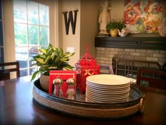 """Fluff Interior Design - Omaha, NE  We love to do """"functional"""" centerpieces like this one! It's pretty, but it also serves a purpose AND frees up cabinet space by putting the plates right on the table. This is a great example of Fluff's tagline in action, """"Decorating for REAL life!"""""""