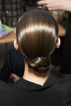 The ultimate cheat for walking out of the house with wet hair (or completely fixing a bad hair day) is this slick chignon hairstyle. Use a serum or gel to slick back hair, then create a twisted chignon at the nape of your neck, securing with bobby pins. Spray an old toothbrush with hairspray and comb down any flyways that may be sticking out.