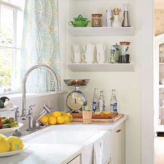 Real-Life Redo: Hardworking Small Kitchen    {Narrow, 6-inch deep shelves turn an empty wall next to the sink into a coffee niche.}    Wall shelves: Wedge Wall Shelf in White from CB2; cb2.com.   Curtain fabric: Cranley in Aqua Nutmeg (BP100554) by GP & J Baker through Lee Jofa (leejofa.com), available through DCOTA Design Services; 954-921-7575.   Sink: Dickinson Apron-front, Undercounter Kitchen Sink (K-6546-4U) by Kohler; kohler.com.   Faucet: HiRise Deck Mount Bridge small kitchen designs, faucet, kitchen gadgets, small kitchens, wall shelves, curtain fabric, farmhouse sinks, kitchen sinks, open shelving