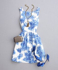 Blue floral patterned dress with bateau neckline, blue heels, necklace and clutch