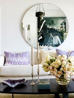 traditional and modern elements mix with a round mirror, gold candlesticks and amethyst