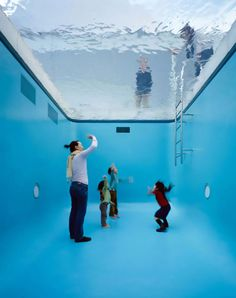 An extraordinary and visually confounding installation…Erlich constructed a full-size pool, complete with all its trappings, including a deck and a ladder.    When approached from the first floor, visitors were confronted with a surreal scene: people, fully clothed, can be seen standing, walking, and breathing beneath the surface of the water.