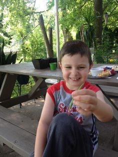Tyler happily tasting beans fresh from his container garden.