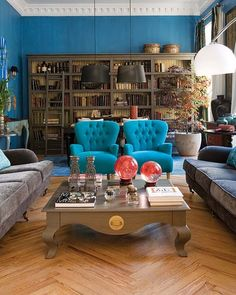 Turquoise chairs with gray sofas, nice.