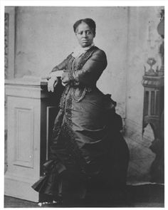"""Lucretia Marchbanks, who earned praise and a good living as the finest chef in the Black Hills. This photo is in the Adams Museum in Deadwood, SD. [ Ava Speese recalled that when her parents moved to Nebraska in 1907, her mother, Rosetta, drove one of the group's three wagons. """"She took care of her own team, greased the wagon wheels, and she was just turned sixteen."""" The necessity of community effort enabled women to enjoy a measure of independence.]"""