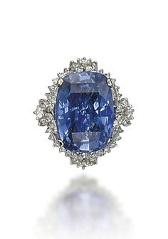 A SAPPHIRE AND DIAMOND RING  Set with a cushion-shaped sapphire, weighing approximately 25.47 carats, to the brilliant and baguette-cut diamond base