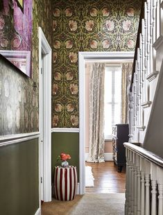 The hallway is decorated with a mix of earthy olive green paint and a similarly-toned William Morris wallpaper.