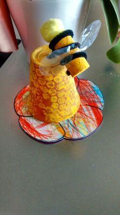 Een bijtje op een korf. Afdruk op bloempot met bubbelplastic. Kurk schilderen en afwerken met pijpenrager. Vleugeltjes, gezichtje geven en klaar. Afwerking een bloem kleuren. een bloem