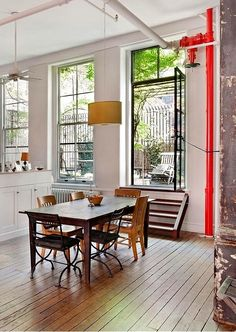 Love the clean and simple lines, hardwood floors, exposed piping, and what appears to be an entrance into a private courtyard. New York loft...wherelse?