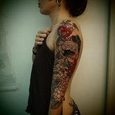 guy le tatooer   beautiful flower sleeve.  I love it when there's just a little bit of red in a black tattoo.