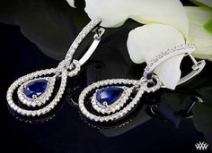 "Splendid in every way, these elegant ""Diamond and Blue Sapphire"" Drop Earrings are guaranteed to dazzle and delight. Beaming with 152 round-ideal diamond melee (1.10ctw; G/SI1) and two sumptuous pear shaped blue sapphires (1.55gtw) these lovelies are definite head-turners"