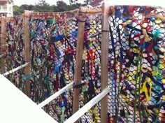 Fence weaving using ribbon/cloth strips - great outdoor art project. Outdoor Art Projects For Kids, Camera, Fenc Weav, Garden, Fence Weaving