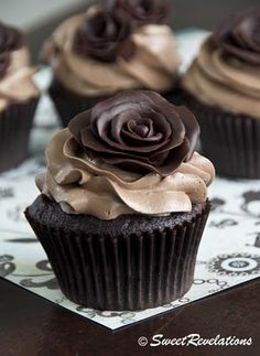 Imagine this, but with plum-colored frosting between the chocolate flower and the cupcake. Is it more feasible to do cupcakes than giant wedding cakes of doom?