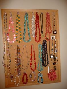 Hanging necklaces on a board with thumb pins.