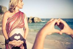 Cute pregnancy picture at the beach with husband's hands forming a heart shadow onto wife's belly.