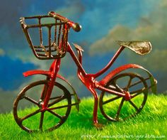 A tiny red bicycle to roll through your miniature fairy gardens.