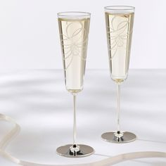 Bedecked with beautiful bows, this festive kate spade new york champagne flute set features silver-plated stems. From Exclusively Weddings.