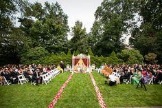 Outdoor Hindu ceremony with rose petal lined aisle via IndianWeddingSite.com