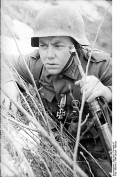Germany. A young German soldier, already decorated with an Iron Cross watches the enemy armed with a MP40 . Russia.1944