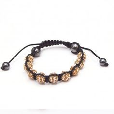 Gold on white shamballa bracelet, contains nine beads each with eighty four crystals embedded in each. Adjustable for different wrist sizes. We use only the highest quality materials.