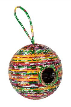 This unique, vibrant birdhouse will have all of the birds flocking to your yard! The Round Recycled Birdhouse is skillfully crafted from upcycled food wrappers and aluminum wire by women working with our fair trade partner Prokritee in rural Bangladesh. In addition to steady, fair wages and safe workplaces, Prokritee provides training in new techniques to help women expand their skills.