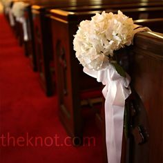 In addition to the simple white hydrangea bouquets tied to the church pews, Johanna had two arrangements of orchids placed at the altar. traditional weddings, pew decor, pew ends, church pews, hydrangea pew, decorations, hydrangea bouquet, flower, hydrangeas