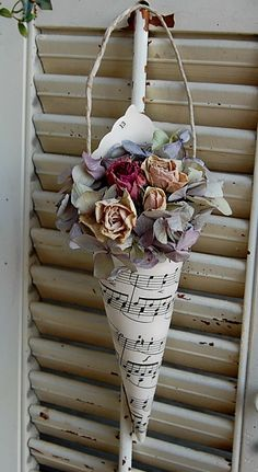 Vintage paper hymnal sheet music cone with dried hydrangea and roses.