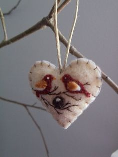 Mini heart felt ornament. It features two birds (mommy & daddy) and an egg in a nest (baby on the way) perched on a tree branch.