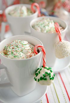 Hot cocoa with marshmallows hanging from candy canes.