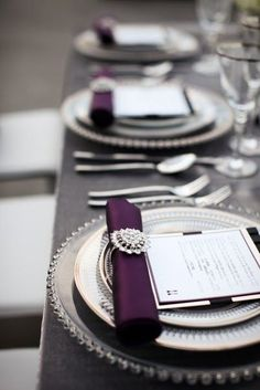 wedding table top with purple napkins in napkin ring with menu and china on grey linen