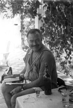 Ernest Hemingway with books and his dog, Negrita, outside his home, Finca Vigia, San Francisco de Paula, Cuba.