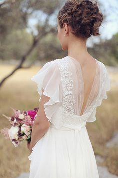 Dropped waist with a beautiful back and flowing sleeves. I need to find this dress...I want to see the front of it.